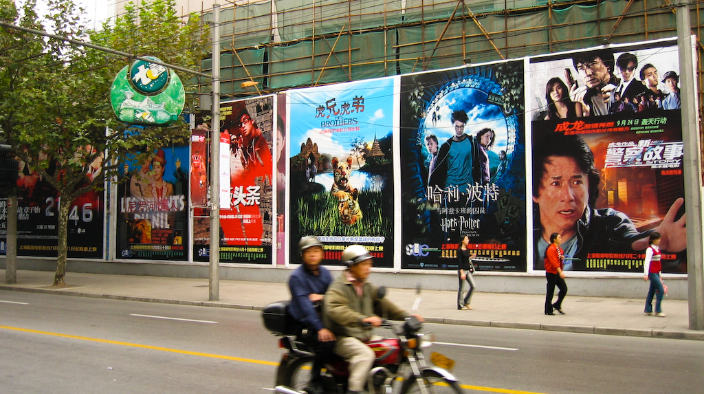Posters of Chinese and Hollywood films line a sidewalk in Shanghai.