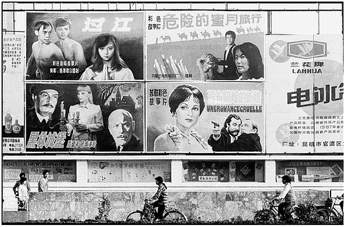 Cyclists and pedestrians under a wall of billboard posters featuring Chinese films and Western films with Chinese titles in 1988