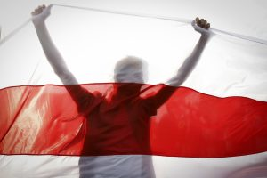 Silhouette of a demonstrator behind a Belarusian national flag